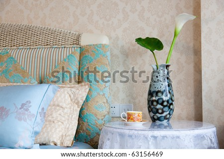 Modern style interior with with bed, pillows, bedside table,teacup and vase - stock photo
