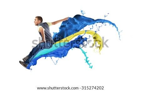 Modern styled dancer jumping over colorful paint splashes - stock photo