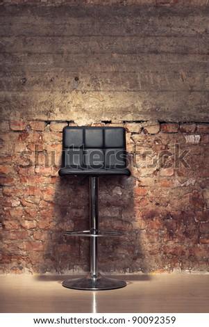 Modern stylish black chair against a grungy brick wall - stock photo