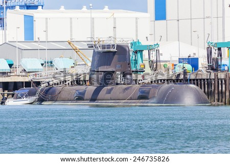 Modern submarine under maintence in a naval shipyard - stock photo