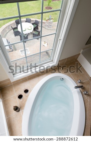 Modern sunken oval bathtub full of clean water in a brown tile surround overlooking a brick patio with outdoor dining through a long view window, viewed from above - stock photo