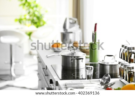 Modern table and electric stove with utensils and vegetables in the kitchen beside window - stock photo