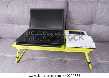 Modern tabletop workstation on a sofa with laptop, stylish eyeglasses, a diary and mobile phone lying on it - stock photo