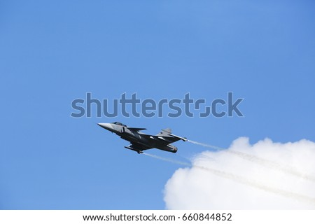 Modern tactical jet fighter flying slow with white smoke trail. Blue sky with clouds in the background.