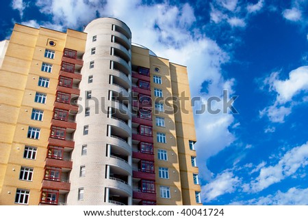 Modern tall residential building on a background of blue sky - stock photo