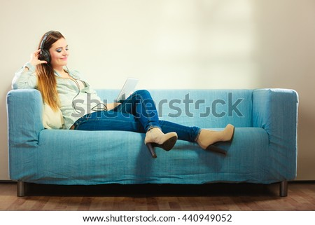 Modern technologies leisure and lifestyle concept. Young attractive woman with headphones sitting on couch using tablet - stock photo