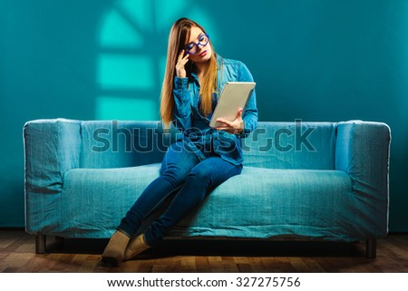 Modern technologies leisure and young people concept. fashionable woman wearing jeans with tablet sitting on couch blue color - stock photo