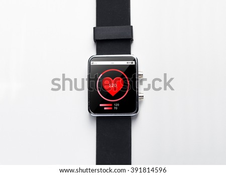 modern technology, health care, object and media concept - close up of black smart watch with heart-rate on screen - stock photo