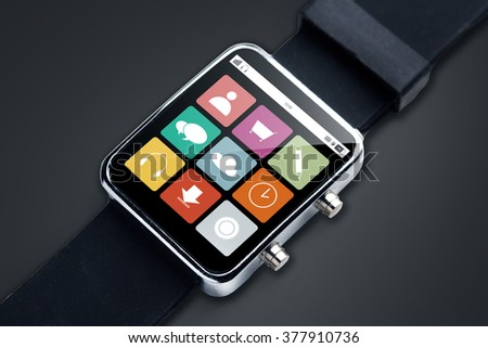 modern technology, object and media concept - close up of black smart watch with app menu icons on screen