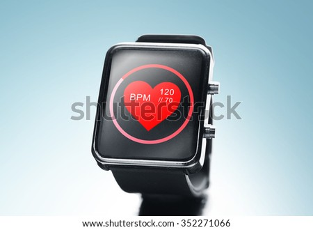 modern technology, object, health care and media concept - close up of black smart watch showing red heart beat icon on screen - stock photo