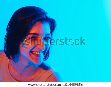 Modern teen contemporary dancer poses in front of the studio background in blue and red tones. portrait horizontal
