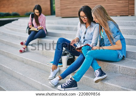 Modern teen girls reading book while sitting on stairs on background of another student - stock photo