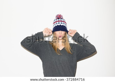 Modern teenage girl in oversize knitted beanie hat and gray sweater. Fashionable young woman posing. Studio portrait, no retouch, no filter. - stock photo
