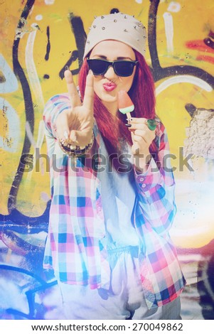 Modern teenage girl with beanie, sunglasses, denim onesie and checkered shirt eating ice cream showing two finger against graffiti painted wall. Vertical, retouched, filter, light leak effect. - stock photo
