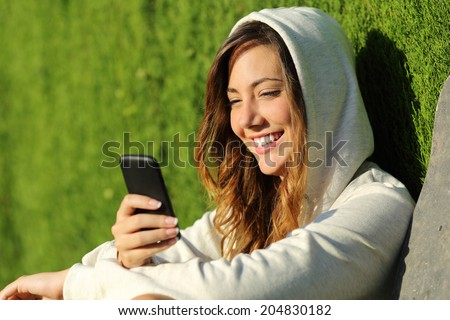 Modern teenager girl using a smart phone in a park with a green background                - stock photo