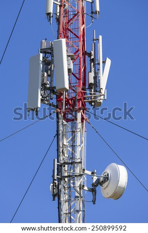 Modern telecommunications tower for mobile communications against the blue sky.