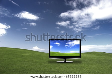 Modern television on a green meadow, showing the colors more beautiful than reality - stock photo