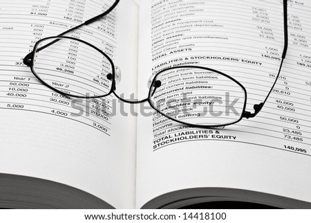 Modern thin reading glasses on open business book with balance sheet numbers - stock photo