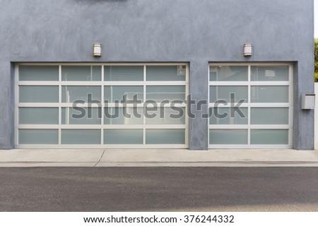 Modern three car garage door with one single door  - stock photo