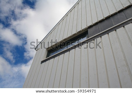 Modern timber clad building with an upward view to a cloudy blue sky - stock photo