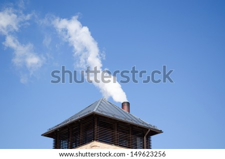modern tin covered roof and white smoke rise from round chimney pipe on background of dark blue sky.  - stock photo