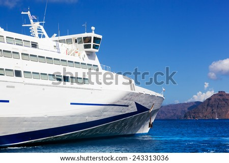 Modern tourist cruise ship sailing on Aegean sea, Santorini island, Greece. Sunny, blue sky. - stock photo