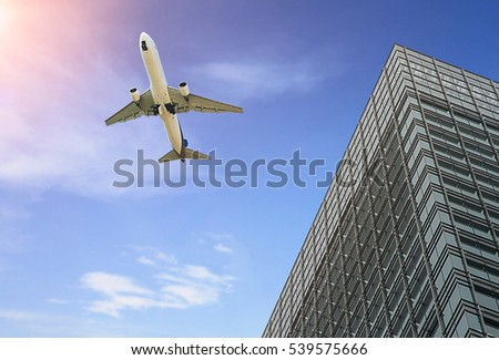 Modern tower with airplane flying over building and sunny