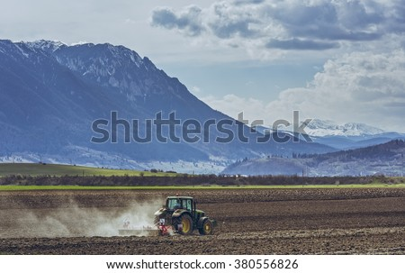 Modern tractor plowing fertile arable field in spring in Transylvania region, Romania. Soil preparation for the spring sowing, crops. - stock photo