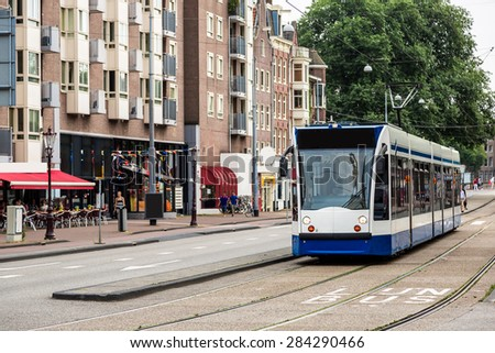 Modern tram in Amsterdam in a summer day