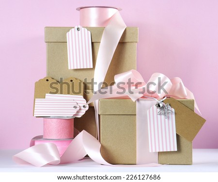 Modern trend natural gift wrapping with natural brown kraft paper boxes and pale pink ribbon with pink and white gift tags against a pink and white background. - stock photo