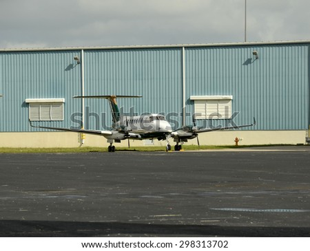 Modern turboprop airplane parked in front of handgar - stock photo