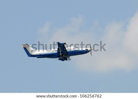 Modern turboprop airplane taking off side view