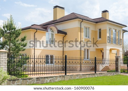 Modern two storey cottage with a wrought fence - stock photo