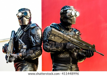 Modern urban soldiers of special elite commando units posing in special black tactical uniform with machine guns with red background - stock photo