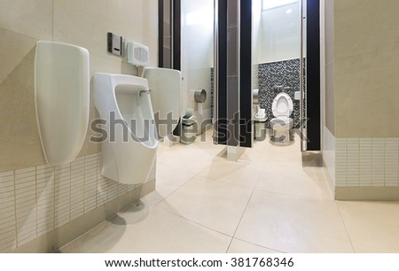 Modern urinals, toilet with mosaic tiles background. - stock photo