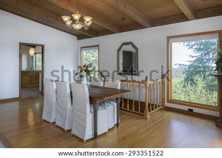 Modern villa, interior with designer chairs, table, beautiful wooden floor and open kitchen next to dining room. View window with trees with staircase and mirror in craftsman home. - stock photo