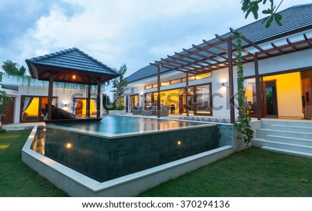 Modern villa outdoor with swimming pool and gazebo at sunset - stock photo