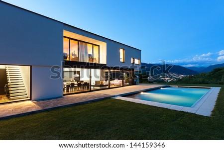 Modern villa with pool, night scene - stock photo