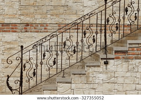 Modern Vintage Style Straight Stone Staircase With Black Wrought Iron Ornate Handrail  Near Tiled Stonewall, Architecture Background - stock photo