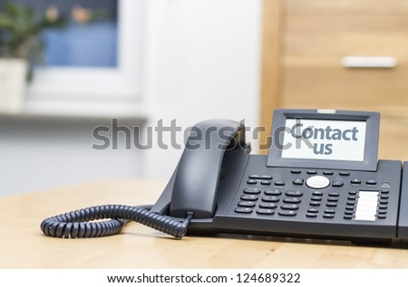 modern voip telephone on wooden desk saying CONTACT US - stock photo