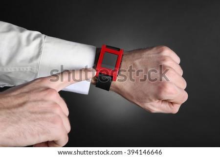Modern watch on a businessman's wrist over black background - stock photo