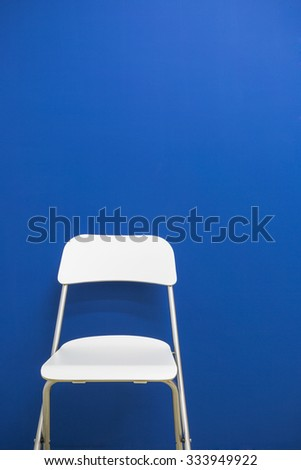 Modern white chair in an empty room with blue background