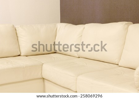 Modern white corner leather sofa taken closeup.