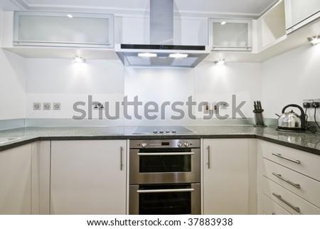 modern white kitchen with gray stone work top - stock photo