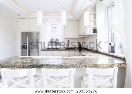 Modern, white kitchen with long granite worktop - stock photo