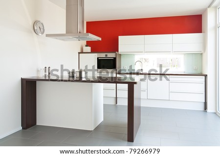 Modern white kitchen with red wall in the back
