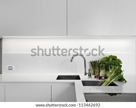 modern white laminate kitchen with vegetables on the white worktop - stock photo