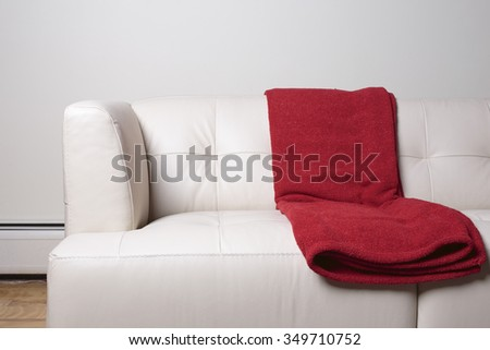 Modern white leather sofa with red blanks. - stock photo