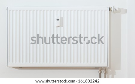 Modern white radiator with thermostat regulation and electronic consumption measurement. - stock photo