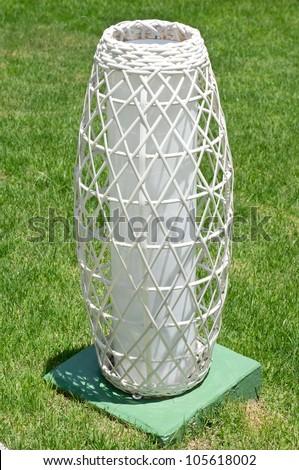 Modern white rattan lamp on lawn - stock photo